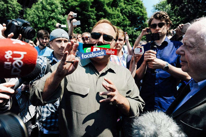 Alex Jones speaks to the media in Watford, Hertfordshire, England, in 2013. A series of social media logos have been digitally pasted over his mouth.