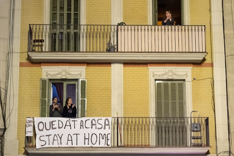 "people on a balcony with a sign that says ""stay home"""
