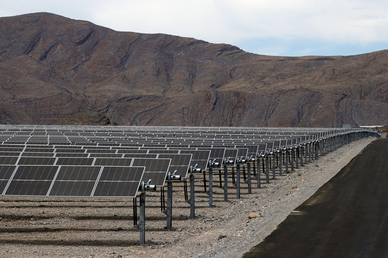 A huge number of solar panels, with a desert mountain in the background.