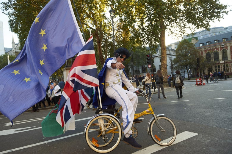 A man dressed as Elvis cycles on a tricycle with European Union, Union Jack, and Welsh flags.