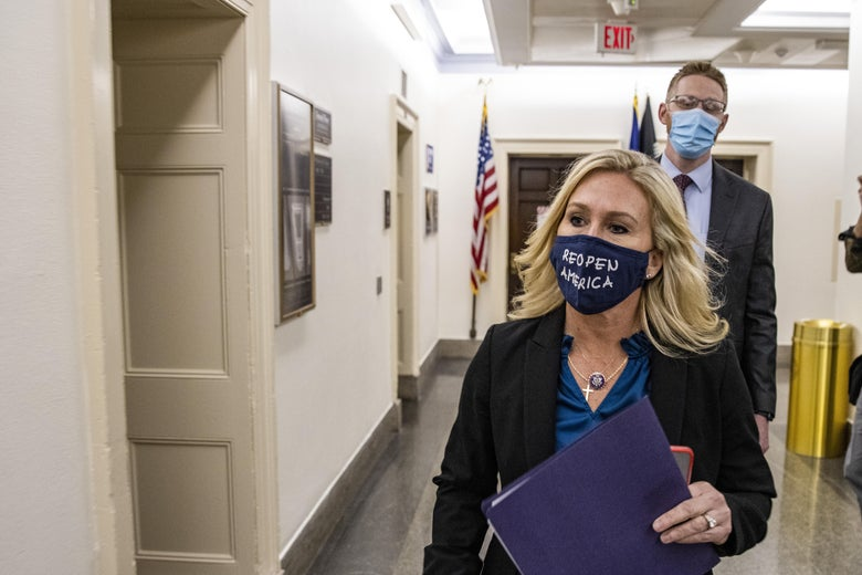 "Greene wears a mask that says, ""REOPEN AMERICA"" as she walks through a hall."