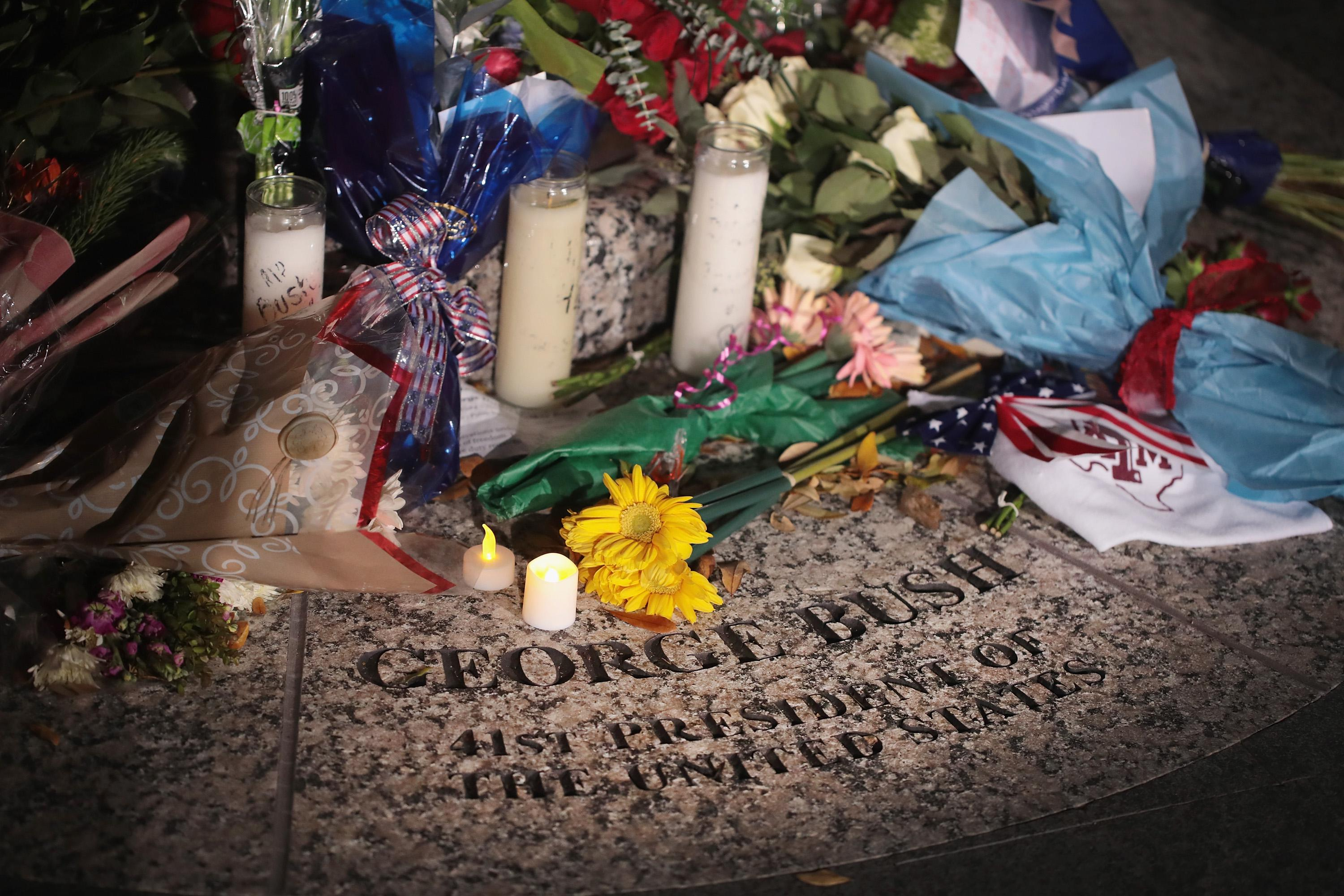 Flowers are left at the base of a statue of President George H.W. Bush on the campus of Texas A&M University outside the George H.W. Bush Presidential Library Center on December 1, 2018 in College Station, Texas.