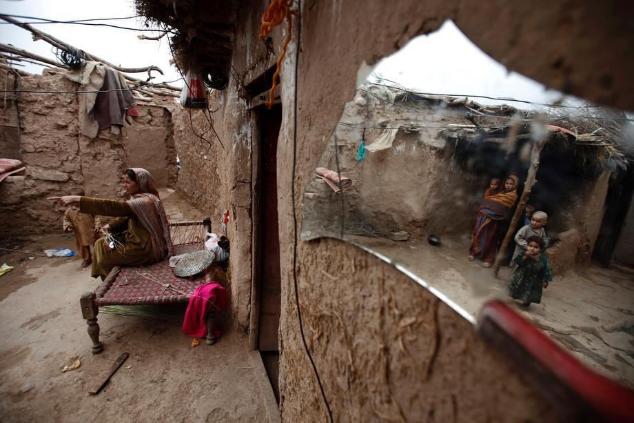 A woman talks to her children at her house in a slum on the outskirts of Islamabad, Pakistan on March 20, 2013.