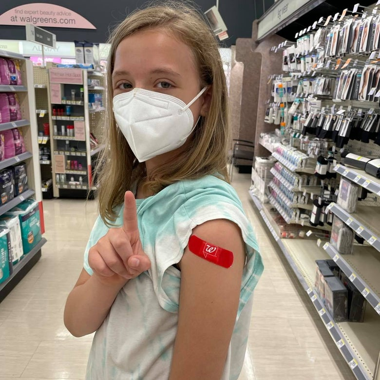 A girl standing in a pharmacy holds her finger up. She is wearing a mask and a rolled up sleeve shows a band-aid on her arm.