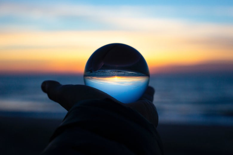 A hand holds a crystal ball in front of a beach sunrise or sunset.