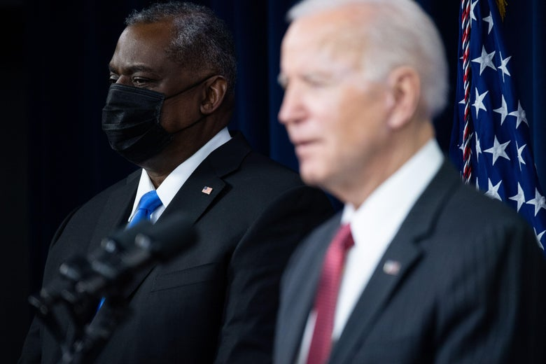 Biden speaks in the foreground and Secretary of Defense Lloyd Austin, wearing a black mask, stands in the background during a press conference at the Pentagon.
