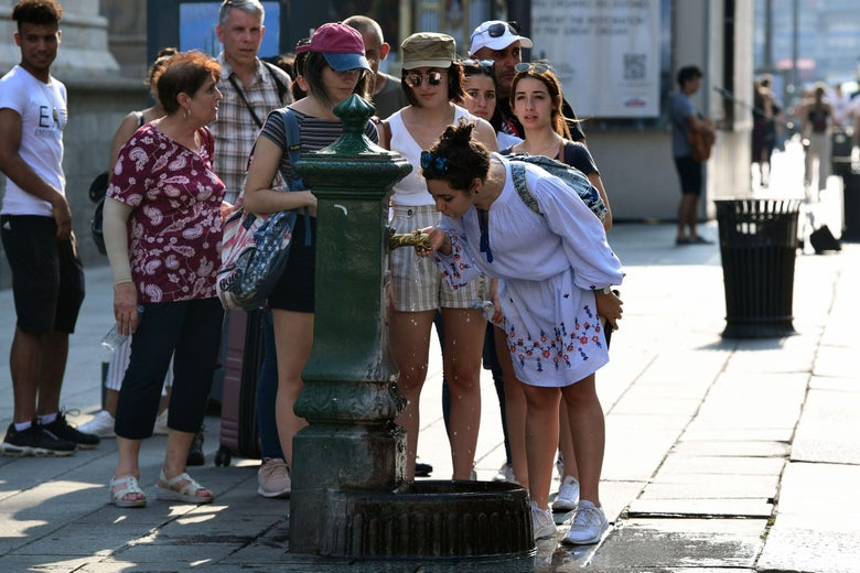 A girl drinking water from a fountain near the Duomo in Italy, while others wait in line.