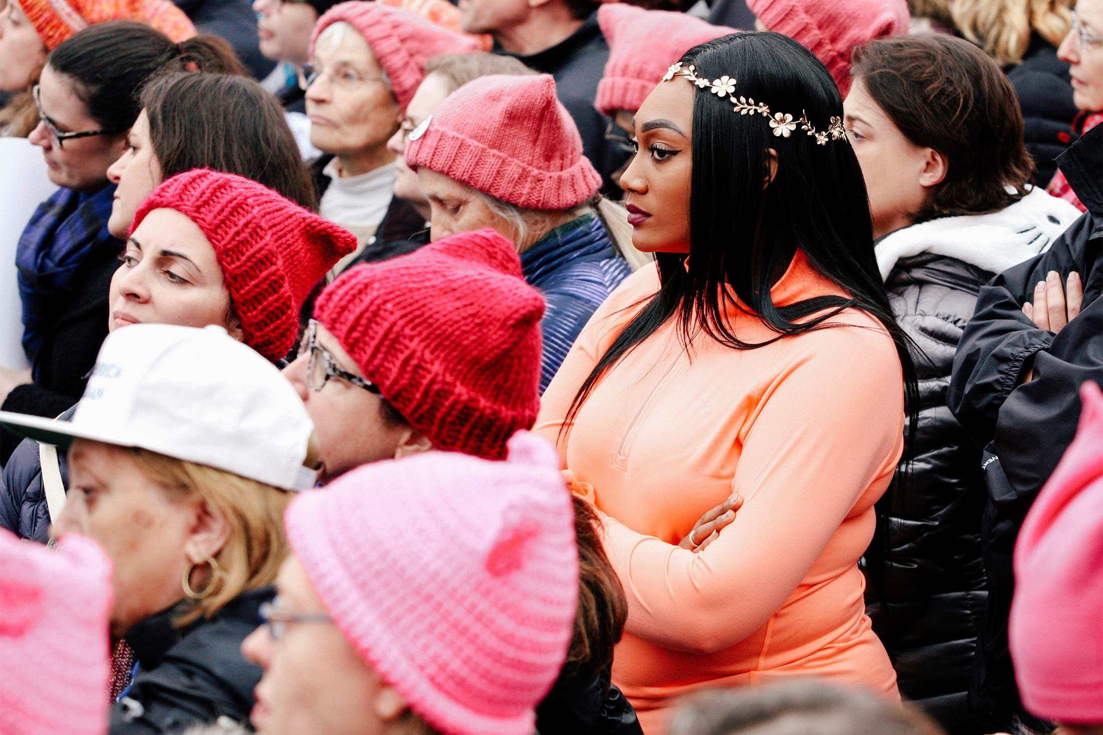 "People wearing ""pussy hats"" and flower crowns listen to speeches at the 2017 Women's March in Washington."