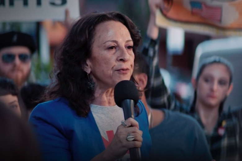 Maria Hinojosa stands in a crowd holding a microphone.