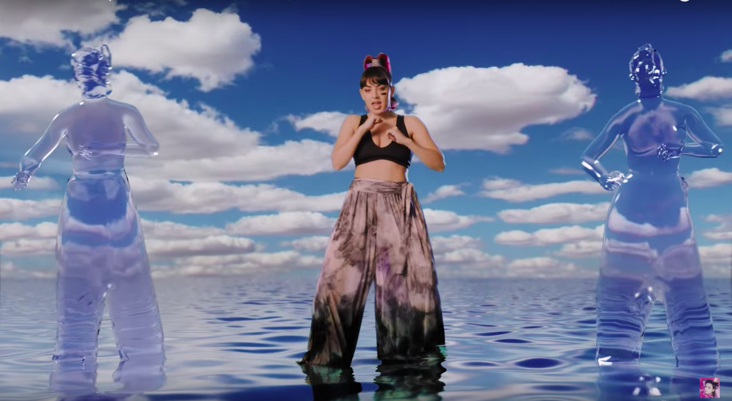 Charli XCX wearing loose pants and a black bralet, standing in glimmering blue water.