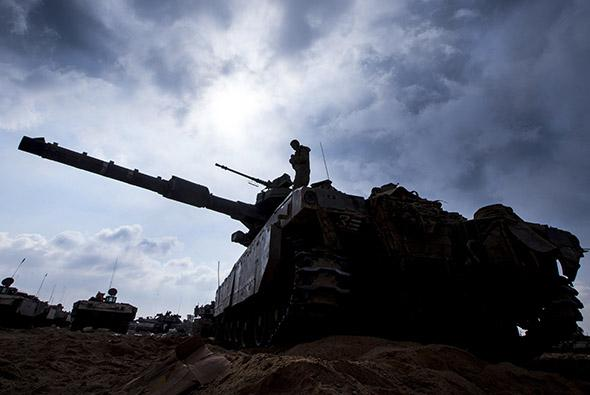 An Israeli soldier prepares a Merkava tank at an army deployment along the border between Israel and the Hamas-controlled Palestinian.