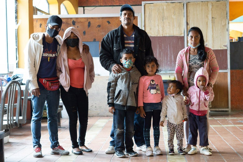 A man and woman stand with four smaller children and two older children off to the side.