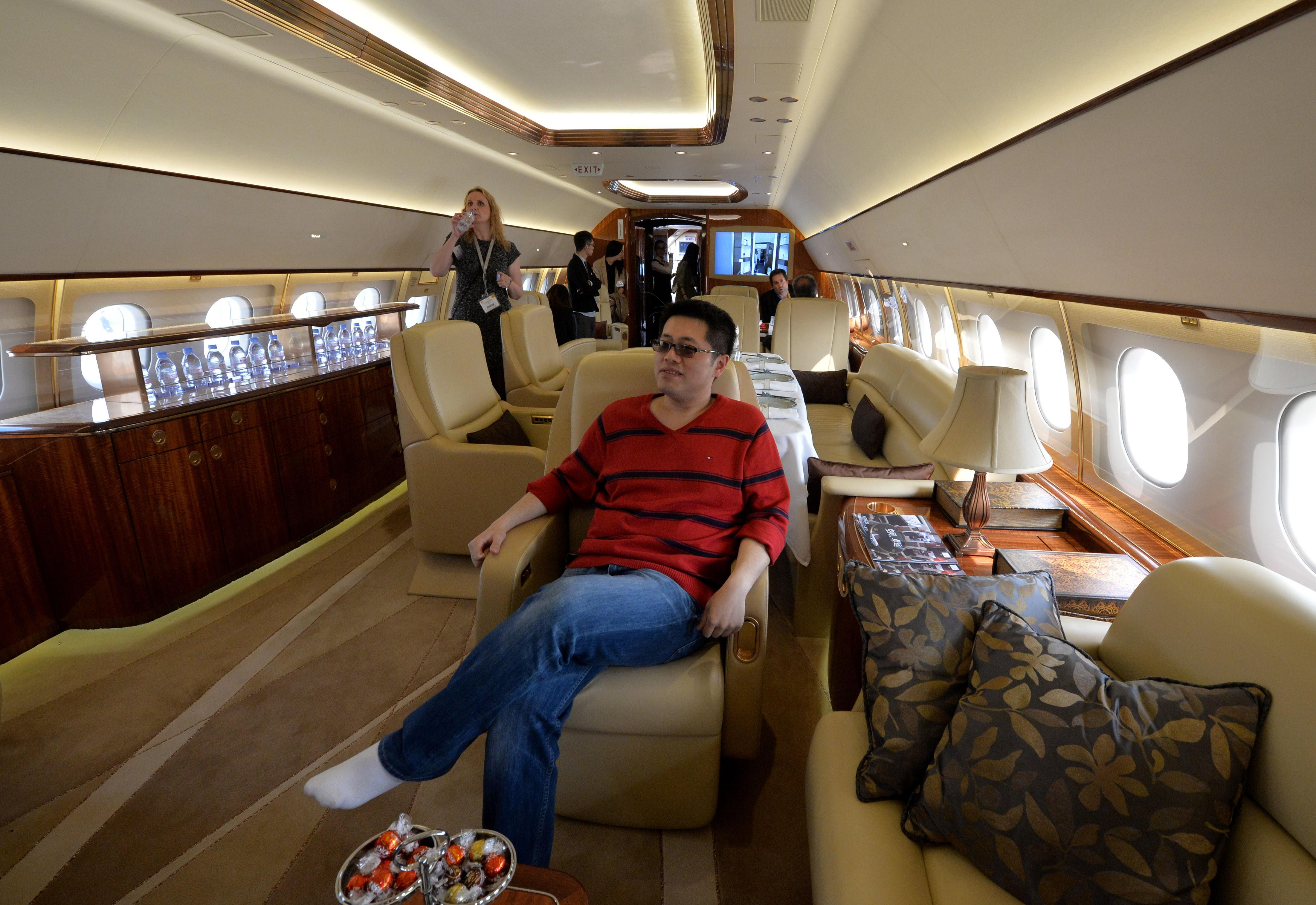 A man tries out the interior on an Airbus A319 private business jet during the Asian Business Aviation Conference and Exhibition (ABACE2014) at the Shanghai Hongqiao airport on April 14, 2014.