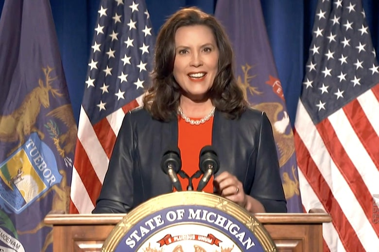 Whitmer, seen in a leather jacket, speaks at a podium bearing a Michigan seal.