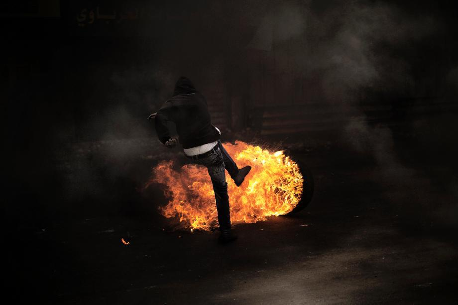 A Palestinian demonstrator kicks a flaming tire during clashes with the Israeli army in the West Bank city of Hebron on April 3, 2013.