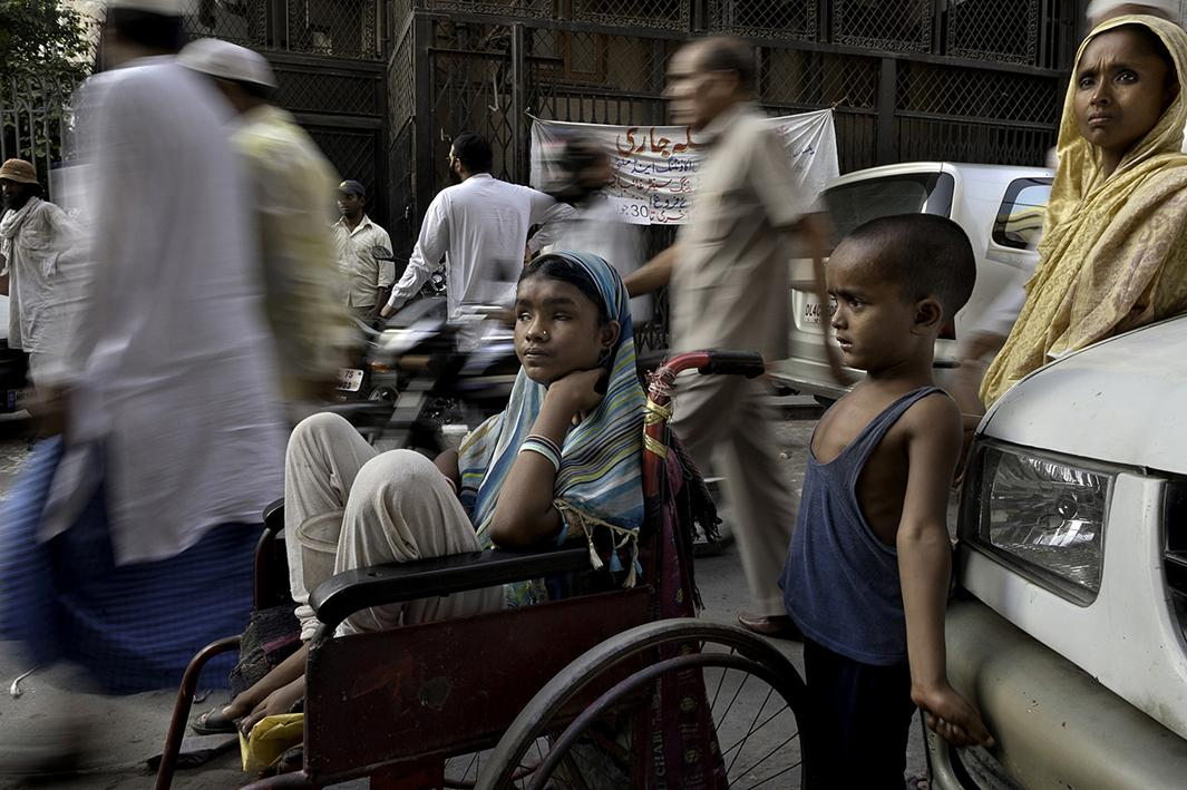 A sea of people passes by Hunupa Begum, 13, who has been blind for the past 10 years and lives close to the Nizamudin Bangala Masjid (Mosque) in New Delhi, India. She begs as the only source of income for her family that consist of a brother Hajimudin Sheikh, 6, center, who suffers fluids that accumulate in his head and her mother Manora Begum, 35, right, who suffers from Asthma, and she has a womb ailment and can't do manual labor. Their father Nizam Ali Sheikh died ten years ago of Tuberculosis. Her wheelchair was donated by a passerby.