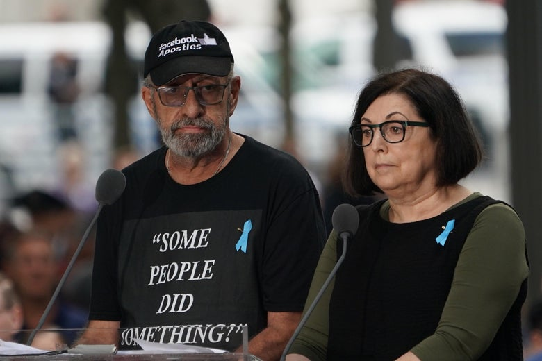 """Nicholas Haros Jr. stands at a podium wearing a T-shirt that says """"SOME PEOPLE DID SOMETHING!"""" A woman stands beside him."""