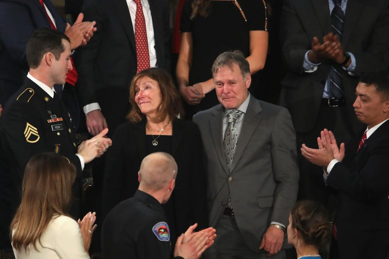 Fred and Cindy Warmbier, both weeping, stand as the surrounding crowd at the State of the Union address applauds.