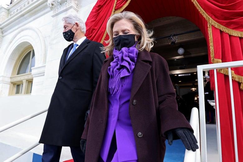 Bill and Hillary Clinton arrive. Hillary is wearing a purple pantsuit under a dark purple coat.