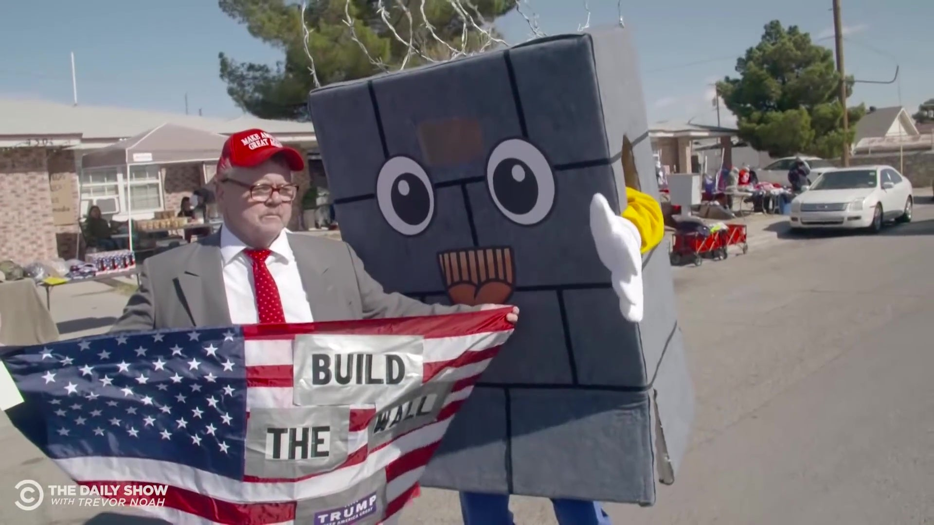 """A man holding an American flag reading """"Build the Wall"""" talks to a Daily Show correspondent dressed up as a cartoon wall."""