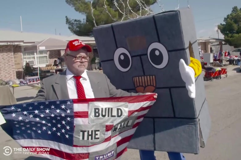 "A man holding an American flag reading ""Build the Wall"" talks to a Daily Show correspondent dressed up as a cartoon wall."