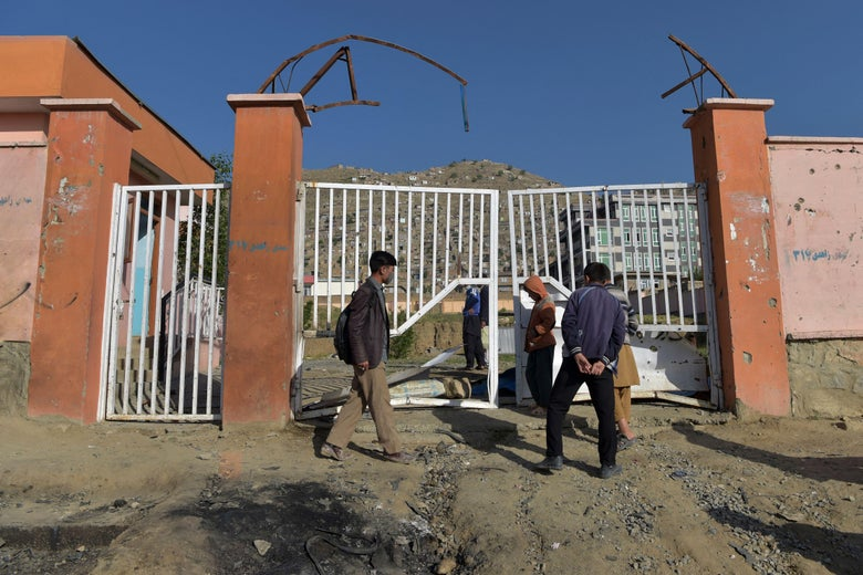 Onlookers stand near the site of yesterday's multiple blasts outside a girls' school in Dasht-e-Barchi on the outskirts of Kabul on May 9, 2021.