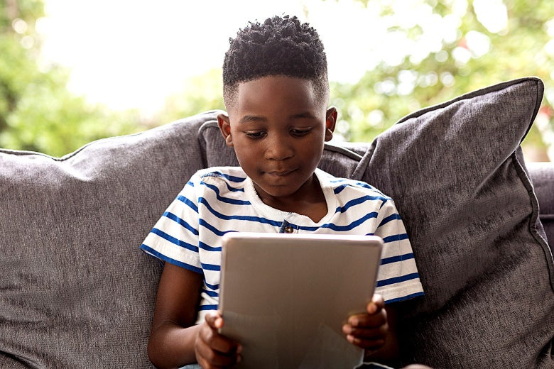 A young Black boy on a couch looking at a tablet.