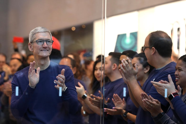 Tim Cook and others applaud inside an Apple store.