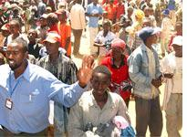 A local official tries to calm a group of Kikuyu refugees during a distribution of clothing         Click image to expand.