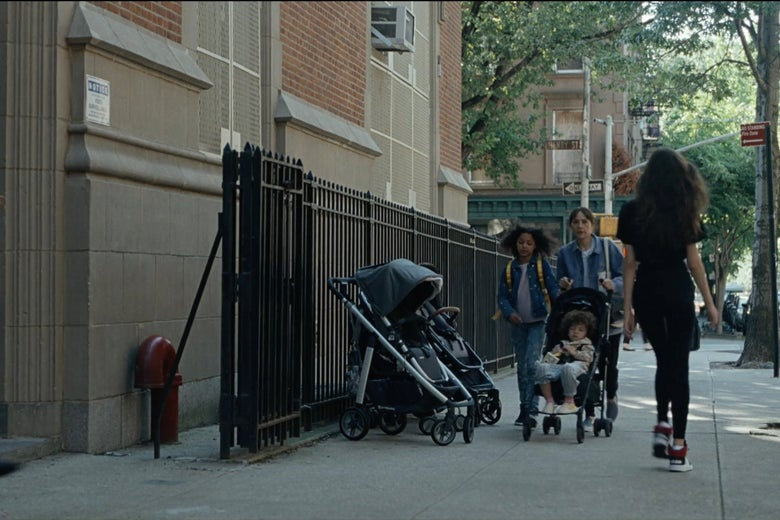 Rashida Jones pushes a stroller with a kid in it and a kid walking beside her down a city street