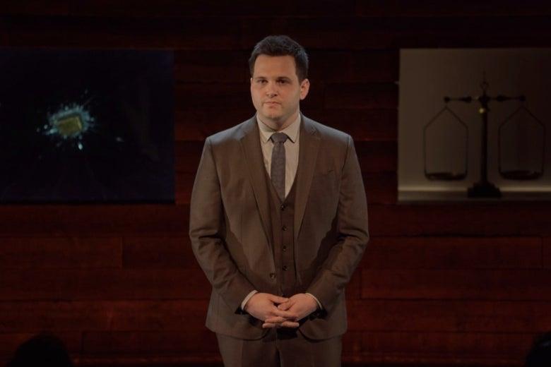 Derek DelGaudio, standing on a stage.