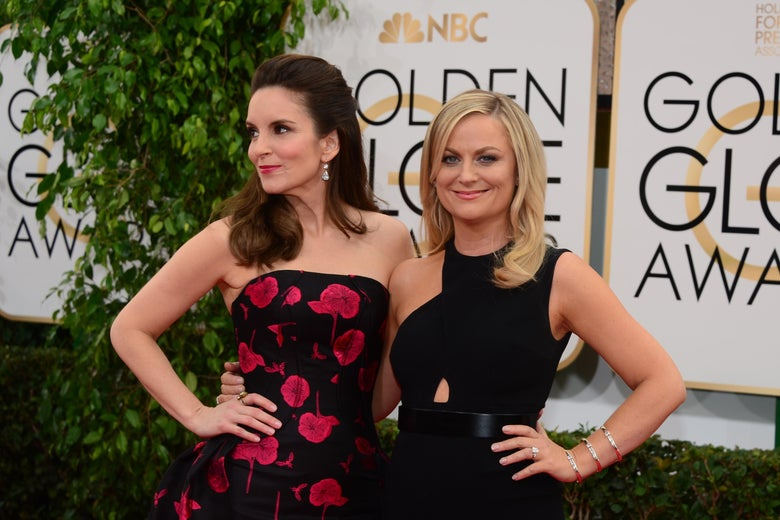 Tina Fey and Amy Poehler on the red carpet for the 2014 globes. Fey is in a black and red dress, Poehler is in black.