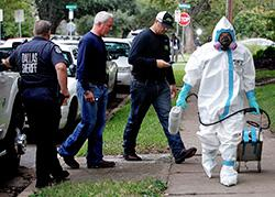 A man dressed in protective hazmat clothing leaves after treating the front porch and sidewalk of the apartment of Nina Pham, Oct. 12, 2014, in Dallas