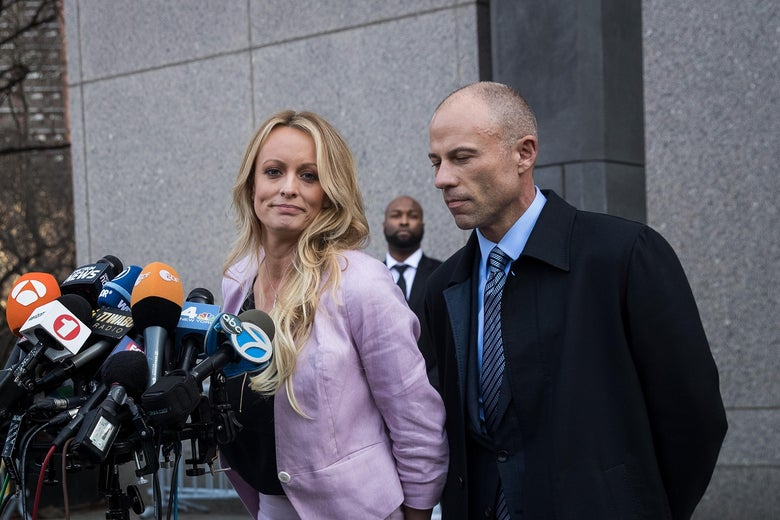 Stormy Daniels and her attorney, Michael Avenatti, stand at a podium of microphones.