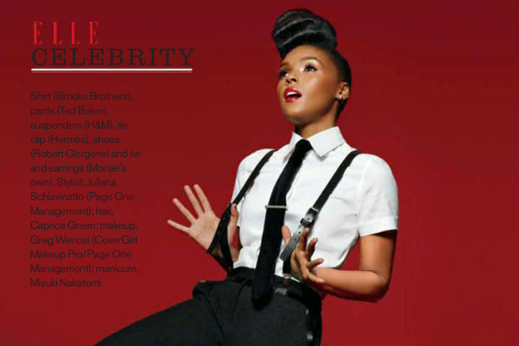 Janelle Monáe, clad in a white, short-sleeved button-down, a black tie with tie pin, and suspenders, puts her hands on the suspenders. She has a euphoric expression.