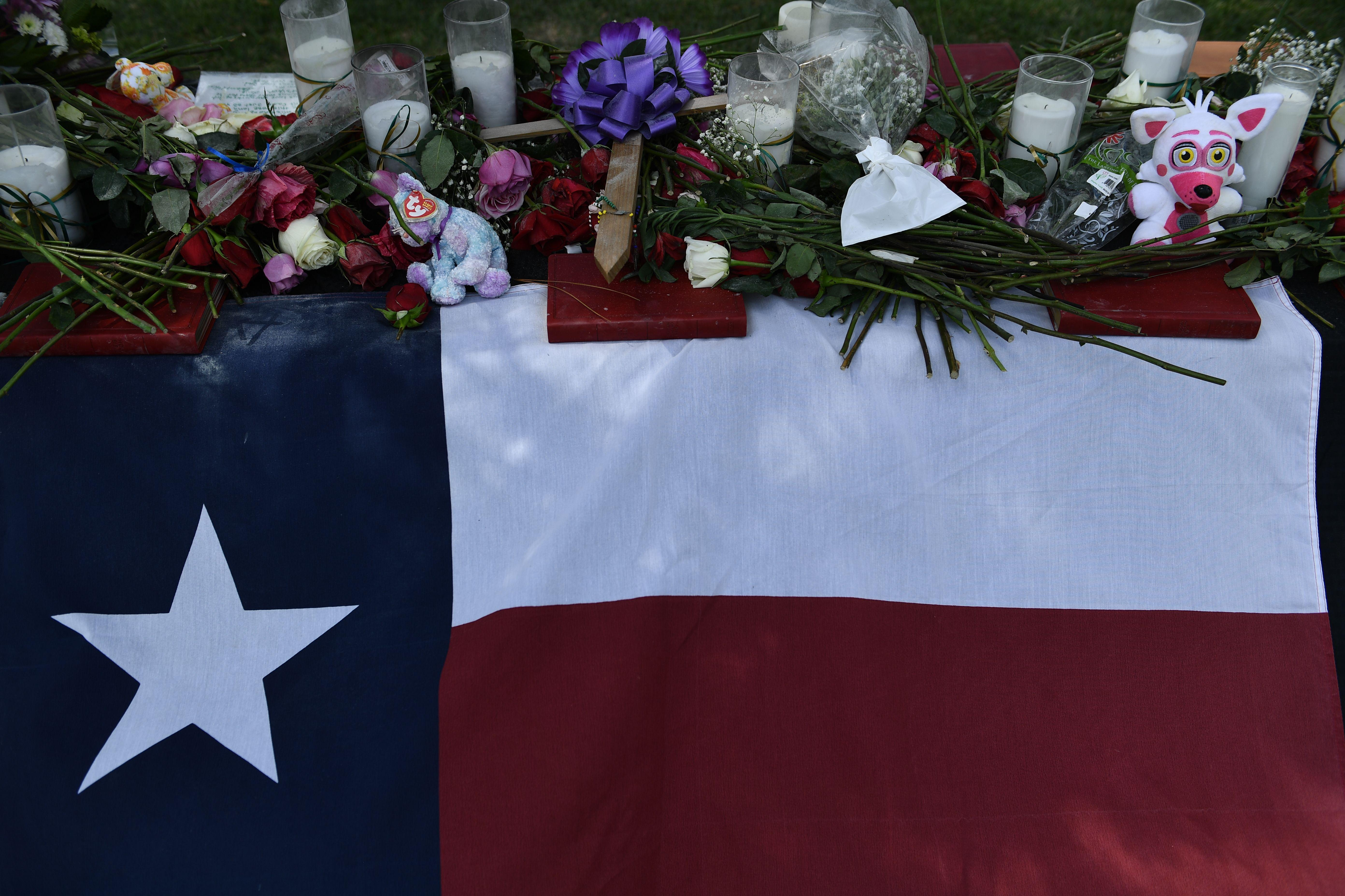 Flowers are left at a makeshift memorial after a vigil at Texas First Bank near Santa Fe High School on May 19, 2018, in Santa Fe, Texas.