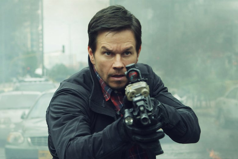 Mark Wahlberg aiming a rifle at the camera in a still from Mile 22.
