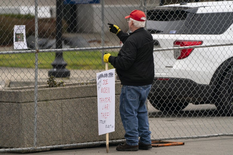A Trump supporter holding a sign outside a gate.
