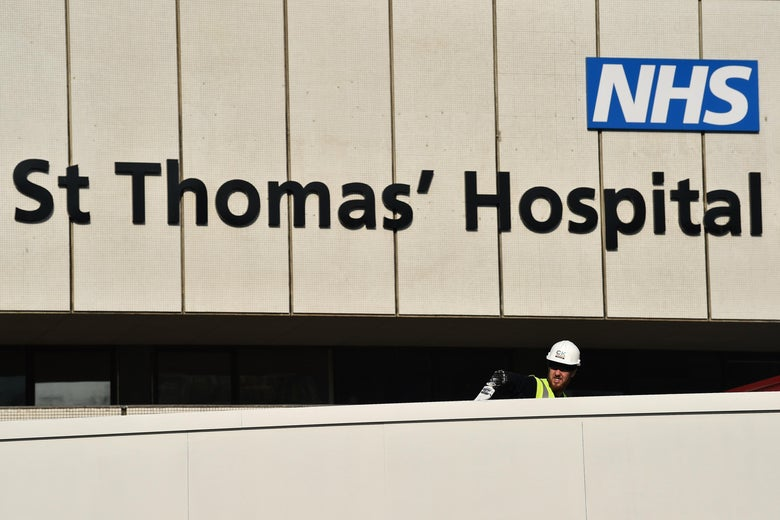 A worker paints a barrier outside St Thomas' Hospital in central London on April 12, 2020, where Britain's Prime Minister Boris Johnson was recovering after contracting the novel coronavirus COVID-19.