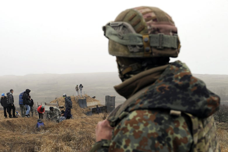 A Ukrainian serviceman looks at activists digging trenches on the coast of the Sea of Azov near the Ukrainian city of Mariupol on November 26, 2018.