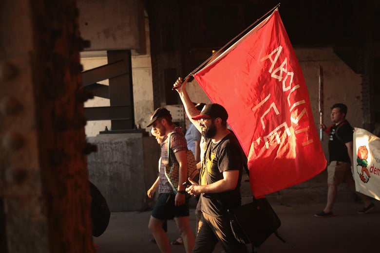 """A demonstrator holds a red flag that says, """"Abolish ICE"""""""
