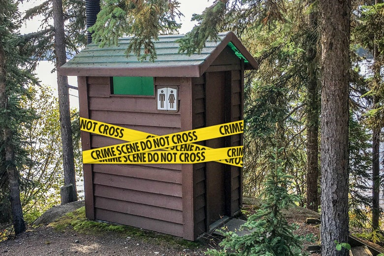Crime scene tape wraps around a public restroom in a wooded area of a park.
