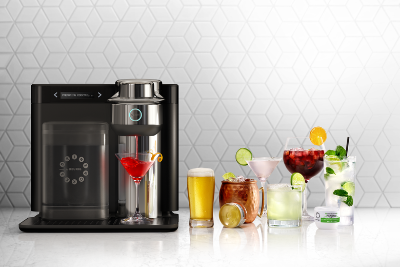 A Drinkworks machine sits on counter next to various drinks including a Sangria, a Moscow Mule, and a beer.