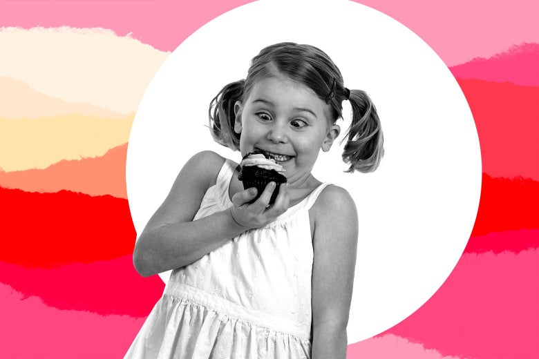 A girl holds a cupcake in her hand and looks eagerly at it.