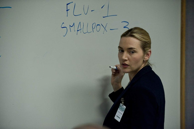 "Kate Winslet holds a marker up in front of a whiteboard. The whiteboard says ""FLU - 1, SMALLPOX - 3."""