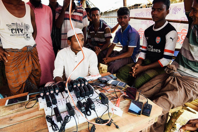 Refugees sit around a charging station of surge protectors with phones plugged in.