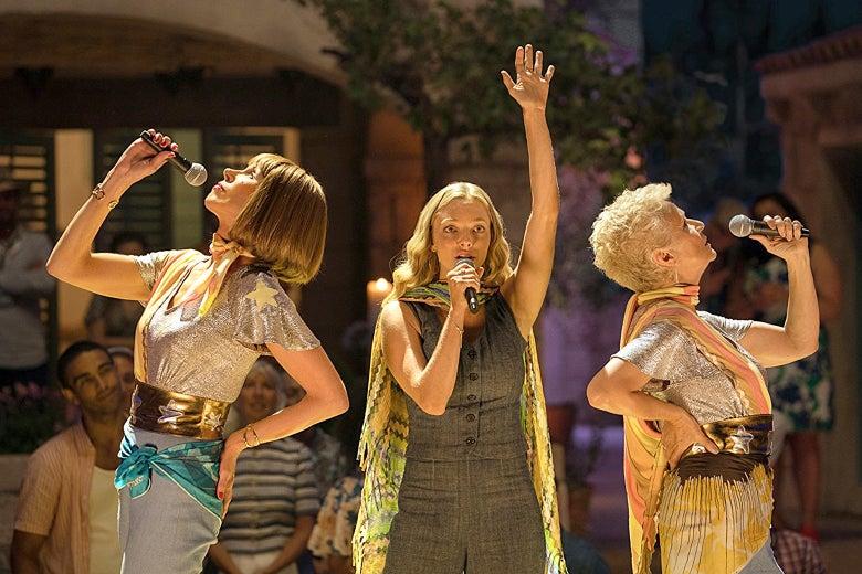 Christine Baranski, Amanda Seyfried, and Julie Walters strike poses while holding microphones in Mamma Mia! Here We Go Again.