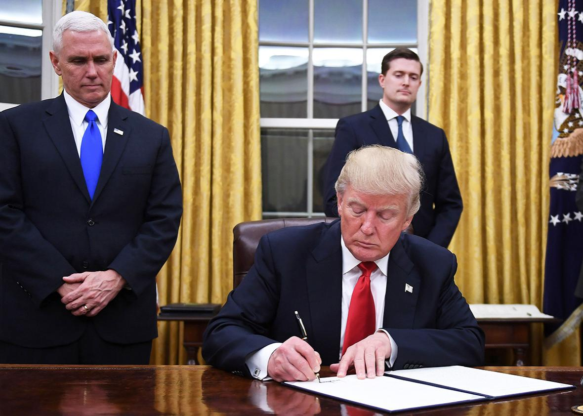 US President Donald Trump signs an executive order as Vice President Mike Pence looks on at the White House in Washington, DC on January 20, 2017.