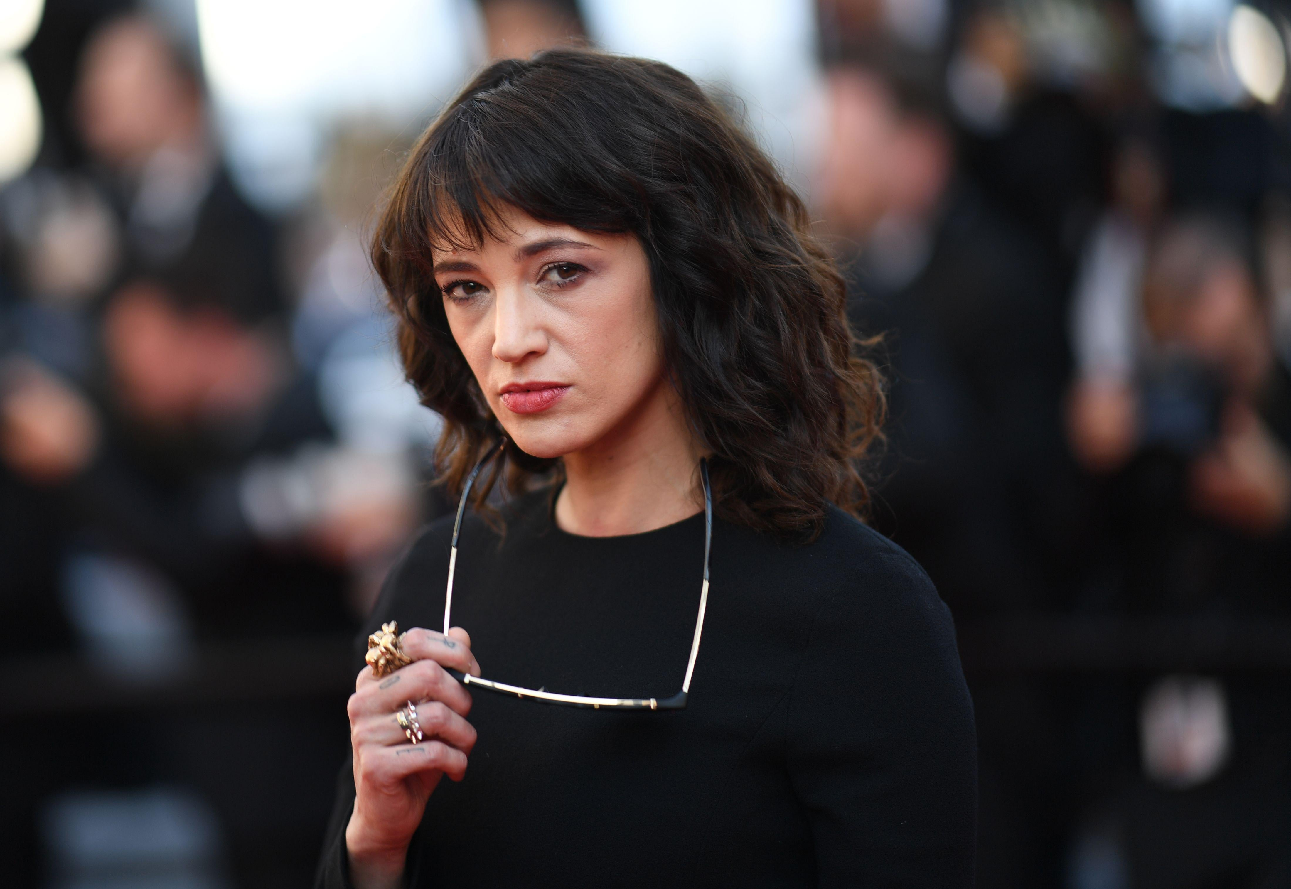 Asia Argento in front of a crowd, holding a pair of sunglasses. She wears black clothing.