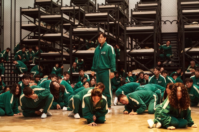 In a bunk bed-filled room, people wearing green and white jumpsuits crouch and sit on the floor. One man with the number 218 on his uniform stands upright.